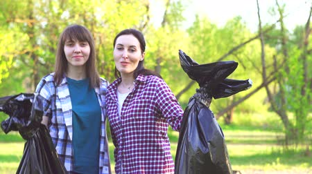 discarded : portrait of two young girls in shirts with plastic bags with garbage in their hands looking at the camera