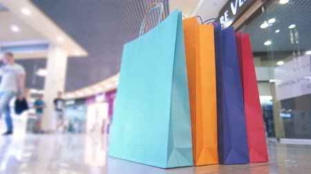 packet : colored shopping bags in the Mall on the background of passing people, timelapse Stock Footage