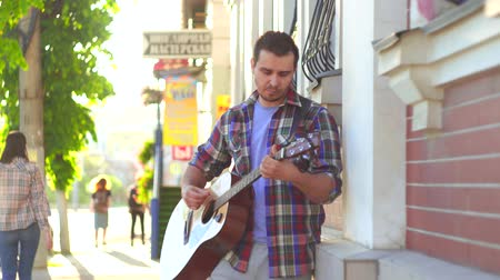 taş duvar : male street musician in shirt playing guitar in city