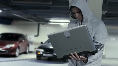 bandido : Car thief with laptop in the underground parking