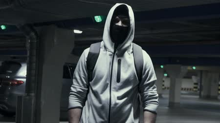 cinayet : Man criminal in the balaclava and the hood in the underground parking Stok Video