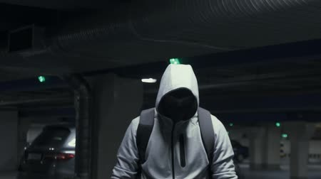 to disguise : Man criminal in the balaclava and hood looking at the camera in underground parking,slow mo