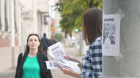 без вести пропавшие : Girl volunteer handing out leaflets about the missing child,slow mo