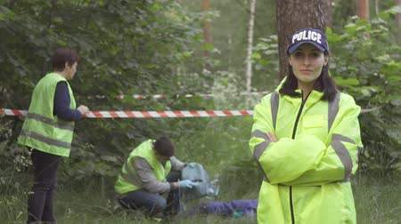 forensic : portrait of a police woman in green uniform on the background of the incident in the Park, looking at the camera