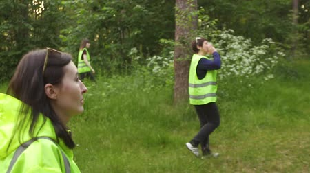 dead forest : a group of volunteers is in the woods in green vests, the search for the missing