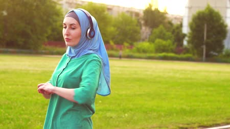 persons : Attractive sporty muslim girl in hijab warms up