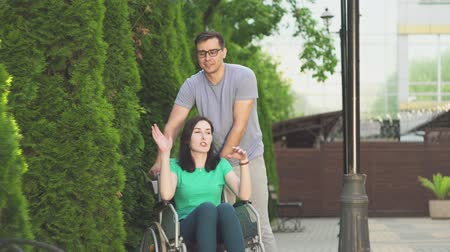 inwalida : young guy and a disabled girl in a wheelchair go for a walk Wideo