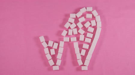 cukros : An unhealthy tooth with caries is lined with refined sugar cubes on a pink background.