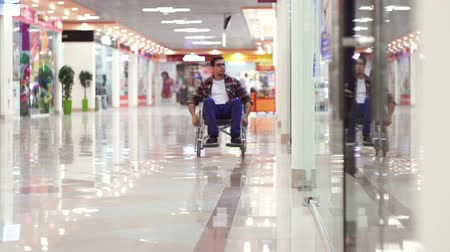 inwalida : Man with a disability in a wheelchair rides to the shopping center and looks at the windows