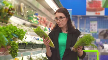 jarmuż : Portrait attractive girl with is faced with a choice of what to buy in the Department with vegetables in the supermarket