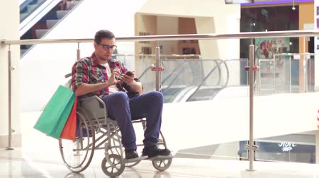 assistência : A disabled man in a wheelchair using the phone in the Mall after shopping