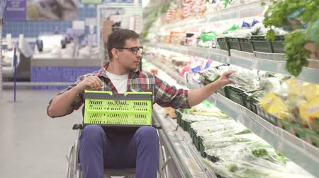 erişilebilirlik : Man with a disability in a wheelchair chooses the goods in the shopping in the supermarket close up