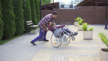 inwalida : Man rolls a happy teenager in a wheelchair in the Park Wideo