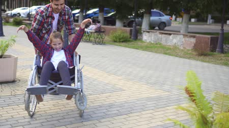 inwalida : Man rolls a happy teenager in a wheelchair in a summer Park.