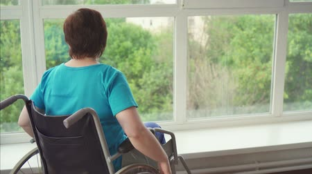 deficientes : Woman with a disability in a wheelchair pulls up to the window