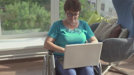 inwalida : Woman in wheelchair working on laptop at home Wideo