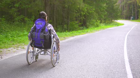 handikap : Disabled girl in a wheelchair traveler rides on the highway