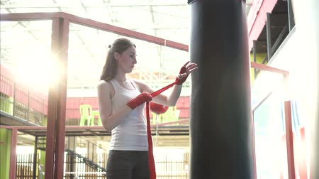 sports nutrition : Woman wraps her hands with a tape of Boxing in a fashionable gym at sunset Stock Footage
