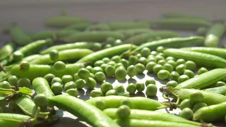 ervilhas : Fresh green peas falling on the table.Close up