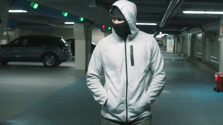 balaclava : Man criminal in black balaclava and hood walks and looks around menacingly.Slow mo Stock Footage