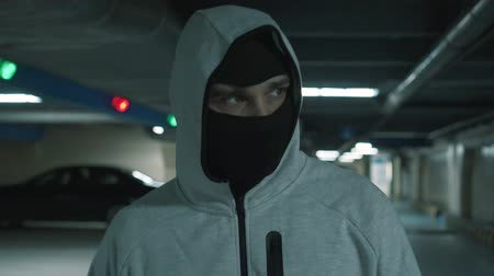 felon : Portrait man in a black balaclava walks and looks menacingly at the camera. Stock Footage