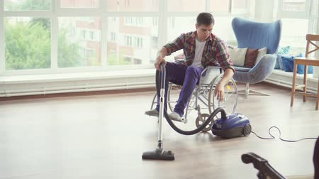 biscate : Man in a wheelchair cleaned with a vacuum cleaner
