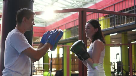 хит : Woman boxer works out with trainer in the gym.Close up