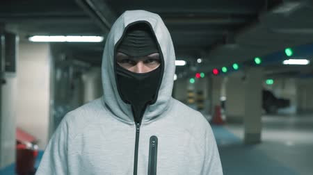 balaclava : Portrait man in a black balaclava walks and looks menacingly at the camera.Slow mo