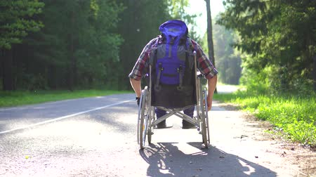 deficientes : Disabled man in a wheelchair traveler rides on the highway