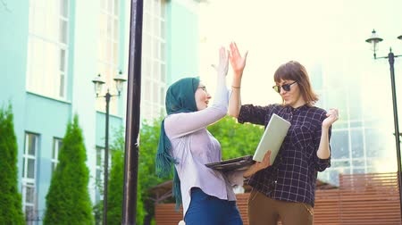 malaya : Muslim student in hijab and her friend are happy looking at laptop sunflare.Slow mo
