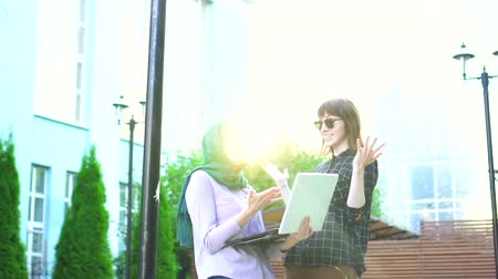 winnings : Muslim girl in hijab and her friend are happy looking at laptop Stock Footage