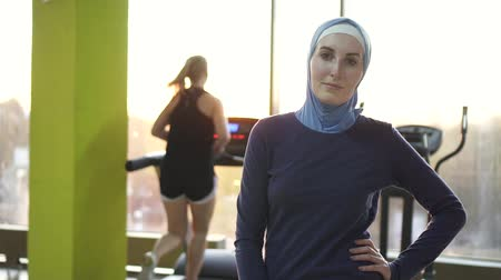 religion health : Portrait of a young muslim girl in a scarf in a stylish gym,sunflare.Slow mo Stock Footage