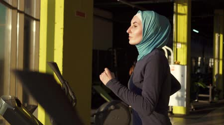 fulllength : Portrait of a sports muslim woman in a scarf on the simulator in the fitness room