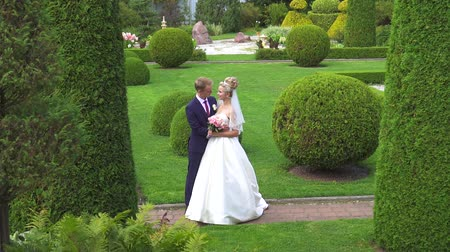 beautiful flowers : portrait of a couple of newlyweds in a beautiful garden