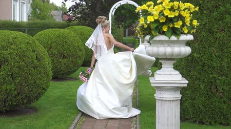 obřad : the bride in a white dress,spinning in slow motion in a beautiful garden