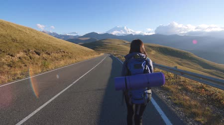 podróżnik : Girl tourist with backpack behind and with a bottle of water goes on the road to the mountains rear view Wideo