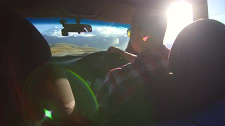 yönlendirmek : Man behind the wheel of a car rides into the mountains,sun ray Stok Video