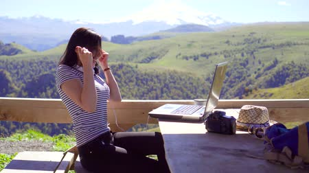 piyango : Girl freelancer with laptop rejoicing success,with mountains in the background Stok Video