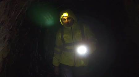 rescuer : Man volunteer with a flashlight in his hand and on his forehead looking for a missing person in a dark cave Stock Footage