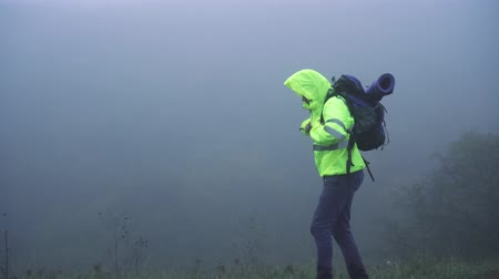 難しさ : Man tourist in signal vest in hood with backpack walking in fog alone,close up 動画素材