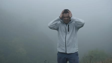 кричать : Frustrated depressed man in depression grabs his head standing alone in the fog