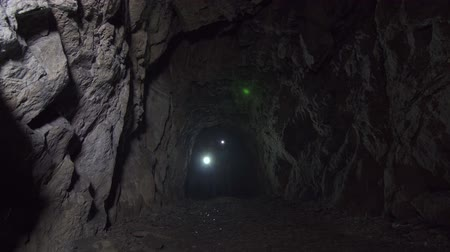 el feneri : Girl and man tourists go through a dark deep cave with a flashlight