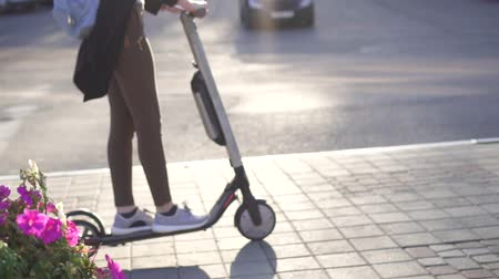skútr : wooman rides an electric scooter on a Sunny city
