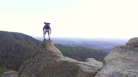 альпинист : Young man tourist with a backpack climbs the mountain and raises his hands up with joy standing on top