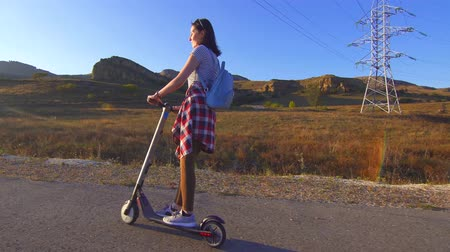 skútr : Young girl rides an electric scooter on the road,sun Dostupné videozáznamy