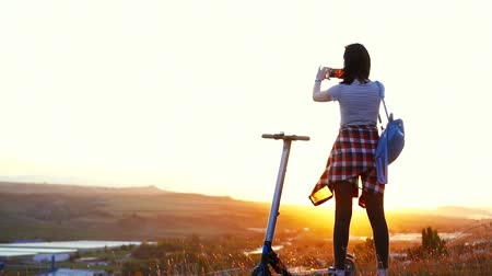mobilet : Girl stands next to the electric scooter taking pictures of the mountain landscape and sunset,slow mo Stok Video