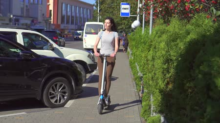 mobilet : Young girl riding an electric scooter on the road in the city, slow mo