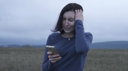 pánik : Young woman reads bad news on a cell phone in bad weather,slow mo