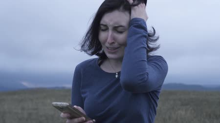 insult : Woman reads bad news on a cell phone and cries in bad weather