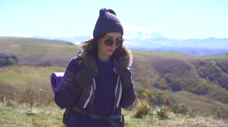 snow on grass : Tourist girl with a backpack walks against the backdrop of the mountains,slow mo Stock Footage